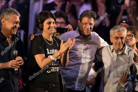 Fernando Haddad, Brazil's presidential candidate for the Workers Party embraces Brazilian singer Caetano Veloso, right, as he poses for a picture with his running-mate Manuela d'Avila and the Brazilian Singer Chico Buarque, left, during a campaign event with popular Brazilian artists and musicians in Rio de Janeiro, Brazil, . Haddad will face Jair Bolsonaro, a far-right congressman, in a presidential runoff on Sunday