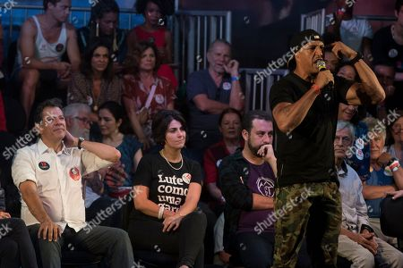 Brazilian singer Mano Brown speaks during a campaign event with popular Brazilian artists and musicians in support Fernando Haddad, left behind, Brazil's presidential candidate for the Workers Party in Rio de Janeiro, Brazil, . Haddad will face Jair Bolsonaro, a far-right congressman, in a presidential runoff on Sunday