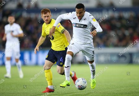 Martin Olsson of Swansea City gets past Harrison Reed of Blackburn Rovers