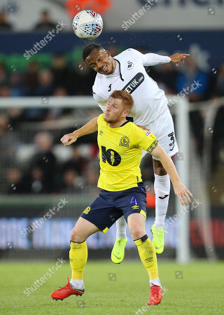 Martin Olsson of Swansea City gets above Harrison Reed of Blackburn Rovers to head the ball