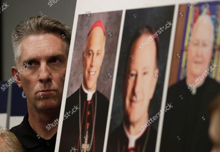 Tom Emens listens to speakers as he stands next to photos of San Francisco Archbisop Salvatore Cordileone, from left, Oakland Bishop Michael Barber and San Jose Bishop Patrick McGrath at a news conference in San Francisco, . A law firm suing California bishops for the records of priests accused of sexual abuse has compiled a report of clergy in the San Francisco Bay Area it says are accused of misconduct