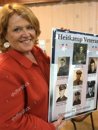 North Dakota Democratic Sen. Heidi Heitkamp holds up a poster of her relatives who have served in the military on in Bismarck, North Dakota. Former Defense Secretary Chuck Hagel is campaigning across the state for Heitkamp, who is viewed as one of the most vulnerable candidates among red-state Democrats in the Senate