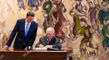 Germany's Speaker of the 'Bundestag' parliament, Wolfgang Schaeuble (R), is watched by Israeli Knesset (Parliament) Speaker Yuli Edelstein (L) as he signs a guest book under a large tapestry done by artist Marc Chagall, which hangs in the Israeli Knesset parliament, in Jerusalem, 24 October 2018.