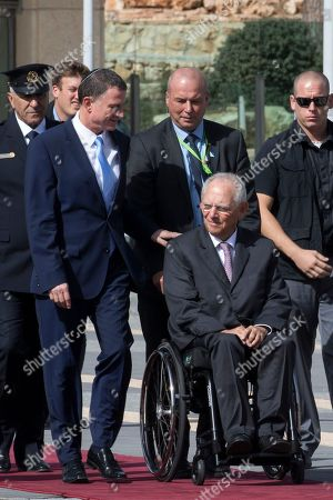 Germany's Chairman of the Bundestag Wolfgang Schaeuble sits in his wheelchair (R) outside the Knesset (Parliament) in Jerusalem during the welcoming ceremony, 24 October 2918. Behind (L) is Israeli Speaker of the Knesset Yuli Edelstein (blue tie).