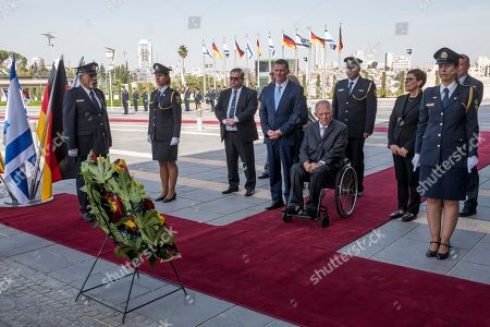 Germany's Chairman of the Bundestag Wolfgang Schaeuble sits in his wheelchair (C-R) after laying a wreath outside the Knesset (Parliament) in Jerusalem during the welcoming ceremony, 24 October 2918.  Next to him is Israeli Speaker of the Knesset Yuli Edelstein (C-L, blue tie).