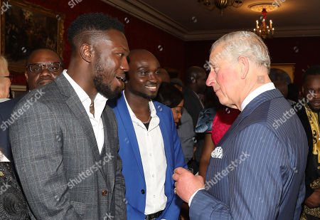 Prince Charles talking with Ghanian Music duo Reggie Zippy known as ' Reggie Zippy 'n' Bollie' at a reception to mark the upcoming tour to Gambia, Ghana and Nigeria at St James Palace
