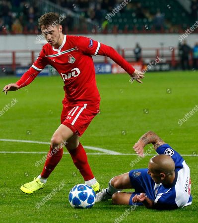 Lokomotiv's Anton Miranchuk, left, and Porto Maxi Pereira challenge for the ball during the Group D Champions League soccer match between Lokomotiv Moscow and FC Porto at the Lokomotiv Stadium in Moscow, Russia