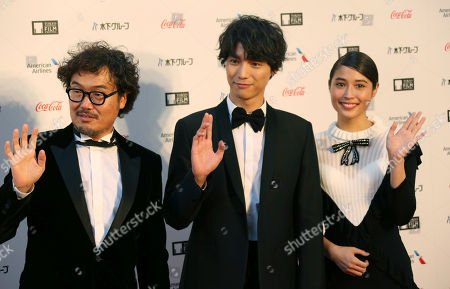 Stock Picture of Film director Koichiro Miki, left, actor Sota Fukushi and actress Alice Hirose pose for photographers during the opening ceremony of the Tokyo International Film Festival in Tokyo