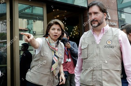 Laura Chinchilla, head of the OAS Electoral Observation Mission and former President of Costa Rica, standing next to fellow observer Gerardo de Icaza, points to their chauffeur outside a hotel after meeting with Workers' Party presidential candidate Fernando Haddad, in Sao Paulo, Brazil, . Haddad will face frontrunner Jair Bolsonaro, in a runoff Sunday