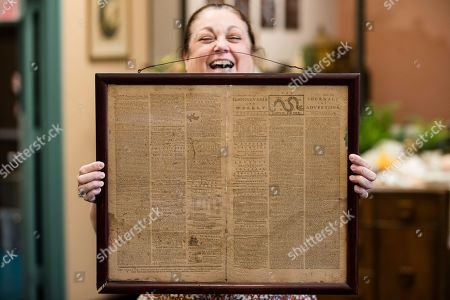 "Heather Randall displays a Dec. 28, 1774 Pennsylvania Journal and the Weekly Advertiser at the Goodwill Industries South Jersey in Bellmawr, N.J., . A quick eye by Goodwill workers in southern New Jersey turned up an original 1774 Philadelphia newspaper with an iconic ""Unite or Die"" masthead"