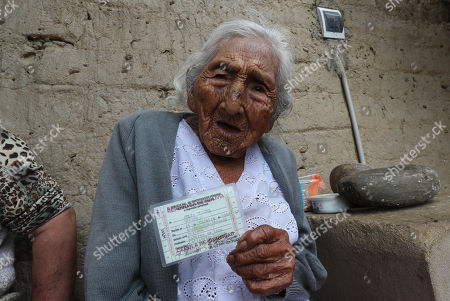 Julia Flores Qolque (R), widely known in Bolivia as 'Mama Julia', shows her ID with her age at her house in Sacaba, 18 kms from Cochabamba, Bolivia, 25 October 2018. Sacaba's City Hall wants to present 'Mama Julia' to the Guiness World Record to be recognized as the eldest person in Bolivia and in the world as she will be 118 years-old on 26 October 2018..