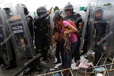 ebed3171bef Stock Picture of A Honduran migrant mother and child cower in fear as they  are surrounded