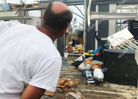 Mark Ward surveys the destruction of his neighbor's mobile home in Bay County, Fla. Ward and his neighbors say that the rural parts of the county have seen little help since Hurricane Michael