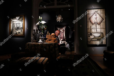 Stock Photo of A bidder looks at pieces of furniture and works of art which belonged to late French industrialist and patron Pierre Berge are on display during the presentation of the 'Pierre Berge: From One Home to Another' auction at Sotheby's auction house in Paris, France, 26 October 2018. The auction runs from 29 October to 31 October.