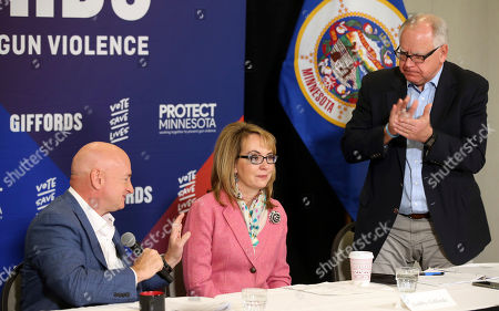 Tim Walz, Mark Kell, Gabby Giffords. Minnesota gubernatorial candidate, Democrat Tim Walz, right, applauds as Capt. Mark Kelly, left, introduces his wife, former Rep. Gabby Giffords as they hosted a roundtable against gun violence, in Minneapolis