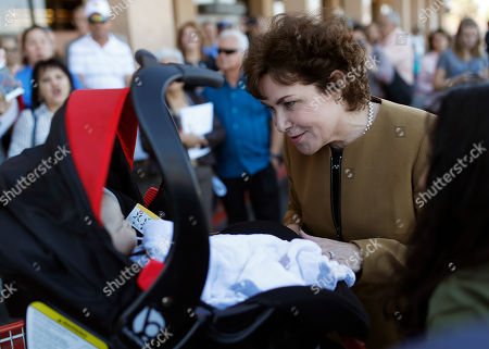 Rep. Jacky Rosen, D-Nev., and candidate for Senate visits with a baby before voting, in Las Vegas