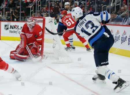 Detroit Red Wings goaltender Jimmy Howard (35) stops a shot by Winnipeg Jets left wing Brandon Tanev (13) during the third period of an NHL hockey game, in Detroit. The Jets defeated the Red Wings 2-1