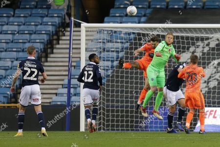 Millwall goalkeeper Ben Amos (13) makes a rare save, watched by Millwall defender Mahlon Romeo (12) and Millwall striker Aiden O'Brien (22) during the EFL Sky Bet Championship match between Millwall and Ipswich Town at The Den, London