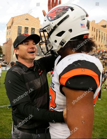 Stock Image of Oregon State head coach Jonathan Smith congratulates Doug Taumoelau (42) following the team's overtime win against Colorado during an NCAA football game, in Boulder, Colo