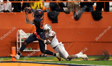 Syracuse wide receiver Taj Harris, left, drags North Carolina State cornerback Chris Ingram across the goal line for an Orange touchdown during the second half of an NCAA college football game in Syracuse, N.Y