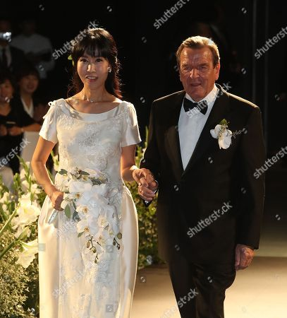 Former German Chancellor Gerhard Schroder (R) and his wife Kim So-yeon (L) walk together during a wedding celebration event in Seoul, South Korea, 28 October 2018.