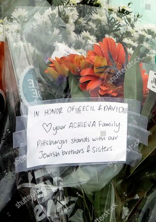 A note honoring shooting fatalities and brothers Cecil and David Rosenthal sits at a memorial at the Tree of Life Synagogue in Pittsburgh, . Robert Bowers, the suspect in Saturday's mass shooting at the synagogue, expressed hatred of Jews during the rampage and told officers afterward that Jews were committing genocide and he wanted them all to die, according to charging documents made public Sunday