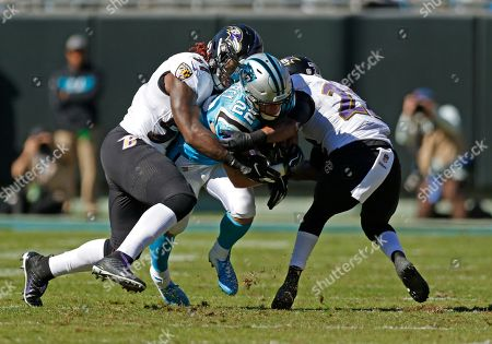 Carolina Panthers' Christian McCaffrey (22) is tackled by Baltimore Ravens' C.J. Mosley (57) and Tony Jefferson (23) in the first half of an NFL football game in Charlotte, N.C