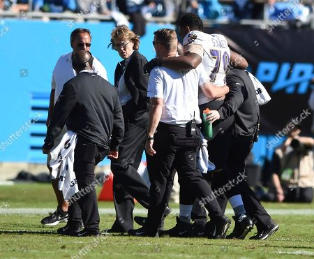 People help Baltimore Ravens' Ronnie Stanley (79) off the field in the second half of an NFL football game against the Carolina Panthers in Charlotte, N.C