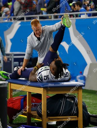 Seattle Seahawks wide receiver Brandon Marshall (15) works with a medical staff to stretch on the sidelines during an NFL football game against the Detroit Lions in Detroit