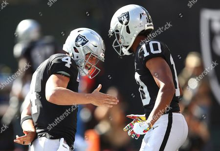 Oakland Raiders quarterback Derek Carr (4) and wide receiver Seth Roberts (10) celebrate after connecting on a touchdown pass against the Indianapolis Colts during the first half of an NFL football game in Oakland, Calif