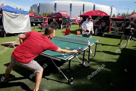 Stock Picture of Arizona Cardinals fans Michael Hoffman, left, and Ryan Rippy play ping pong prior to an NFL football game against the San Francisco 49ers, in Glendale, Ariz