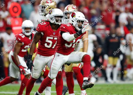 Arizona Cardinals safety Budda Baker (36) and linebacker Josh Bynes (57) celebrate after a sack against the San Francisco 49ers during the second half of an NFL football game, in Glendale, Ariz