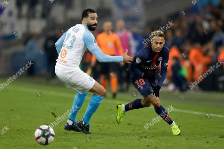 PSG's Neymar, right, and Marseille's Adil Rami challenge for the ball during the French League One soccer match between Paris-Saint-Germain and Marseille at the Velodrome Stadium in Marseille, France