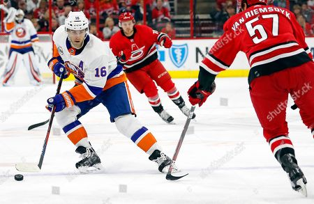 New York Islanders' Andrew Ladd (16) brings the puck up the ice to challenge Carolina Hurricanes' Trevor van Riemsdyk (57) during the first period of an NHL hockey game, in Raleigh, N.C