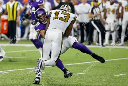 Minnesota Vikings free safety Harrison Smith, left, intercepts a pass in front of New Orleans Saints wide receiver Michael Thomas (13) during the first half of an NFL football game, in Minneapolis