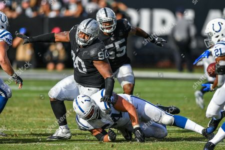 Indianapolis Colts offensive guard Mark Glowinski (64) puts a chop block on Oakland Raiders defensive tackle Johnathan Hankins (90) during the NFL football game between the Indianapolis Colts and the Oakland Raiders at the Oakland Alameda Coliseum in Oakland, CA