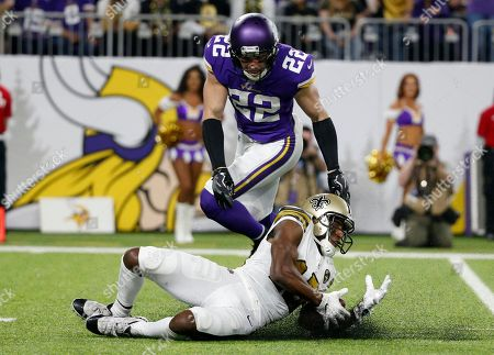 New Orleans Saints wide receiver Michael Thomas catches a pass in front of Minnesota Vikings free safety Harrison Smith (22) during the first half of an NFL football game, in Minneapolis