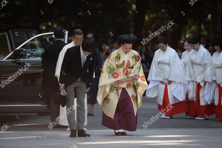 Stock Picture of Japanese Princess Ayako, the third daughter of the late Prince Takamado, and Kei Moriya bow as they arrive at the Meiji-Jingu shrine in Tokyo
