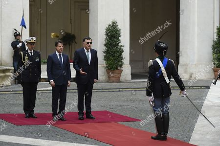 Italy's Prime Minister Giuseppe Conte (L) welcomes the Chairman of the Presidential Council of Libya, Fayez al-Sarraj (R) at the Chigi palace in Rome