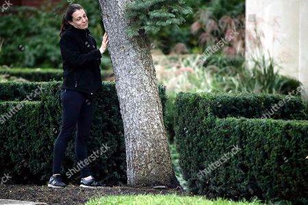 A woman touches a tree as she pauses near a memorial in front at the Tree of Life Synagogue in Pittsburgh, . Tree of Life shooting suspect Robert Gregory Bowers is expected to appear in federal court Monday. Authorities say he expressed hatred toward Jews during the rampage Saturday and in later comments to police