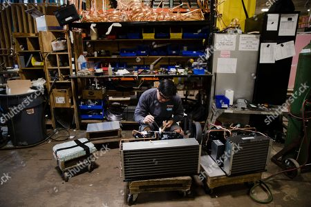 Minh Pham works on a compressor unit at the Howard McCray's commercial refrigeration manufacturing facility in Philadelphia. The experience Christopher Scott, president of Howard McCray, has had suggests that the impact of the tariffs is still playing out