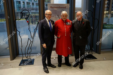 U.S. Ambassador to Britain Woody Johnson, left, Chelsea Pensioner Company Sergeant Major Alan Collins, center, and British General Lord Richard Dannatt, the retired former Chief of the General Staff, the head of the British army, pose for a group photograph to unveil two 6 foot 'Tommy' figures purchased from the 'There But Not There' campaign to commemorate the upcoming centenary of the end of World War I at the U.S. Embassy in London, . World War I ended on November 11, 1918 and 'There But Not There' is the 2018 Armistice project for the charity Remembered