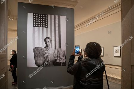 """Jessica White, from San Francisco, takes a snapshot using her phone as she enters an exhibition at the National Gallery of Art of the work of photojournalist, musician, writer and film director Gordon Parks, in Washington, . Her father, the African-American artist Charles White, was a friend of Parks, as well as the subject of one of the photos in the exhibit. Shown is Parks's iconic 1942 photograph called """"American Gothic"""" and portrays Ella Watson who worked cleaning the offices of the Farm Security Administration in Washington"""