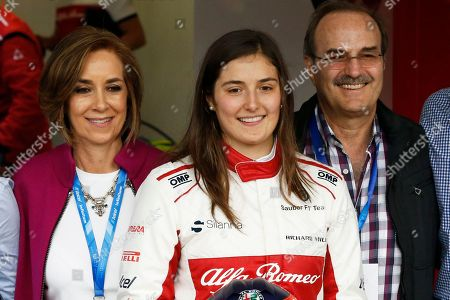 Colombian Formula One driver Tatiana Calderon, center, poses with her parents Maria Clara Noguera, left, and Alberto Calderon, right, as she becomes the first Latin American woman Formula One driver, at the Hermanos Rodriguez racetrack in Mexico City