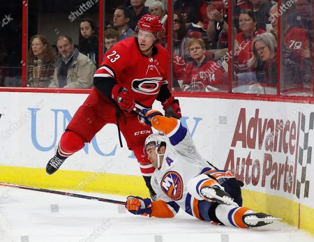 Brock McGinn, Andrew Ladd. New York Islanders' Andrew Ladd (16) collides with Carolina Hurricanes' Brock McGinn (23) during the third period of an NHL hockey game, in Raleigh, N.C