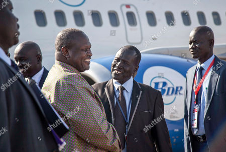 South Sudan's opposition leader Riek Machar, center-left, is greeted as he arrives at the airport in Juba, South Sudan . For the first time since fleeing the war-torn country more than two years ago, Machar returned on Wednesday to take part in a nationwide peace celebration