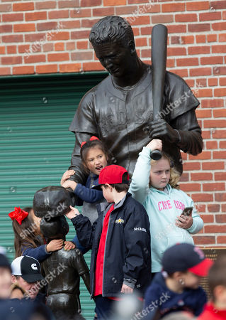 Stock Image of Children climb on the statue of Red Sox Hall of Fame player Ted Williams outside of Fenway Park in an attempt to see the 2018 World Series Champion Boston Red Sox riding on duck boats during their victory celebration parade in Boston, Massachusetts, USA, 31 October 2018. The Red Sox defeated the Los Angeles Dodgers in game five of the best of seven series on 28 October 2018.