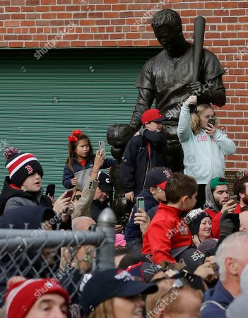 Boston Red Sox fans stand around a statue of Ted Williams outside Fenway Park, waiting to watch the team's parade celebrating the World Series championship over the Los Angeles Dodgers, in Boston