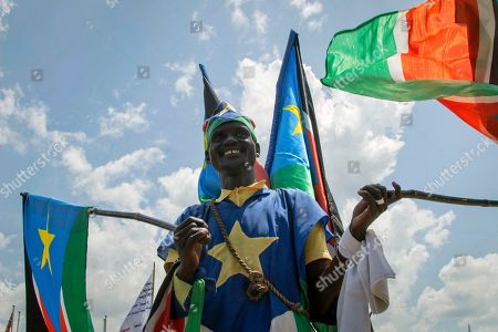 A man waves South Sudanese national flags during peace celebrations in the capital Juba, South Sudan . For the first time since fleeing South Sudan more than two years ago, opposition leader Riek Machar returned on Wednesday to take part in a nationwide peace celebration