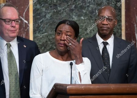Alysia Montano, Jim Carroll, Edwin Moses. Alysia Montano, an American middle distance runner, flanked by Jim Carroll, deputy director of the Office of National Drug Control Policy, left, and Edwin Moses, chairman of the U.S. Anti-Doping Agency, wipes away tears as she recounts her experience at the 2012 Olympics when she finished behind two Russian runners using performance-enhancing drugs, during a White House event aimed at reforming the World Anti-Doping Agency, in Washington